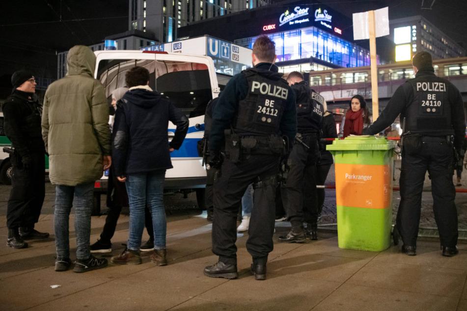 Polizisten und Passanten stehen an Silvester 2019 an einem Kontrollpunkt am Alexanderplatz. (Archivbild)