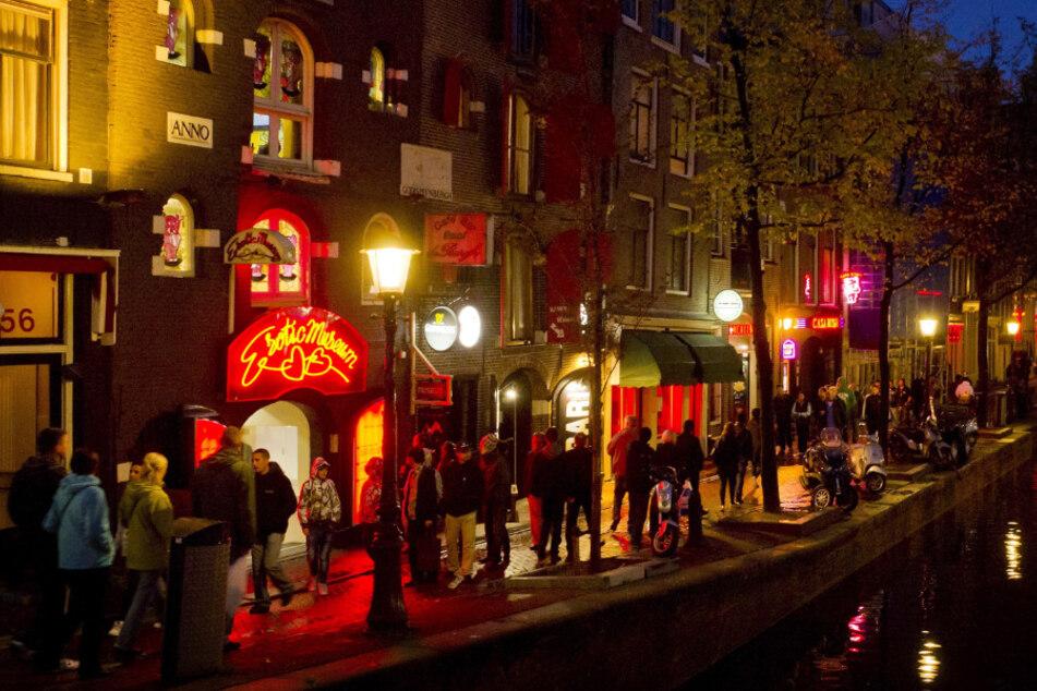 Menschen schlendern am Abend an einer Gracht entlang durch den Rotlichtbezirk De Wallen. (Archivbild)