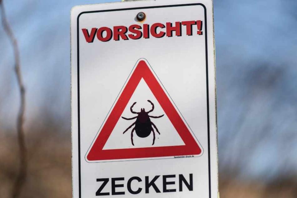 Ein Schild weist auf die Gefahr von Zecken hin.