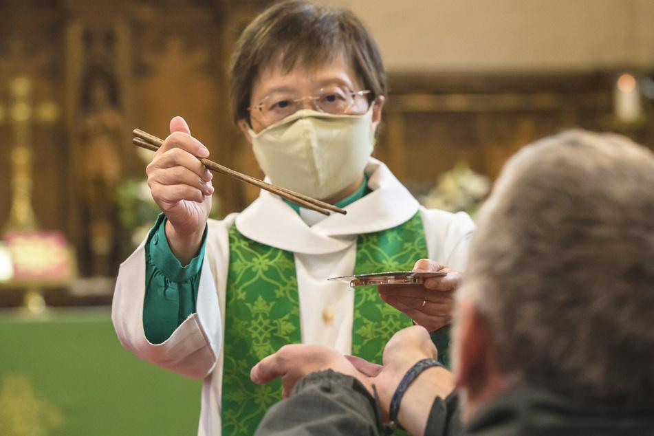 Großbritannien, Winston: Eileen Harrop, Pfarrerin der Kirche von England, benutzt in der Corona-Krise lange Essstäbchen, um Gläubigen bei der heiligen Kommunion das Brot zu reichen.