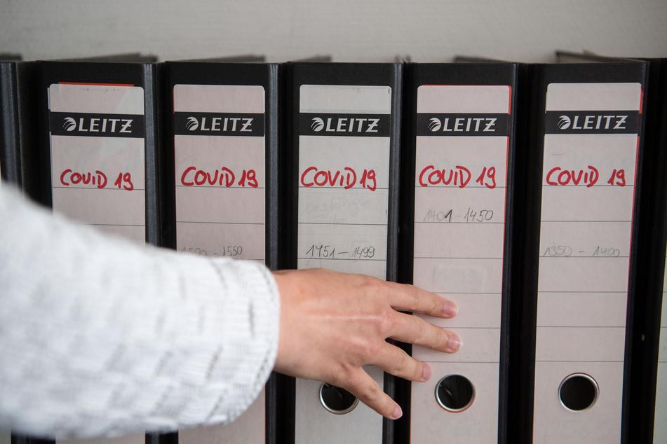 Die Koordinatorin des Kontaktpersonenmanagement im Gesundheitsamt des Landkreises Esslingen schiebt einen Ordner in eine Regalreihe zurück.