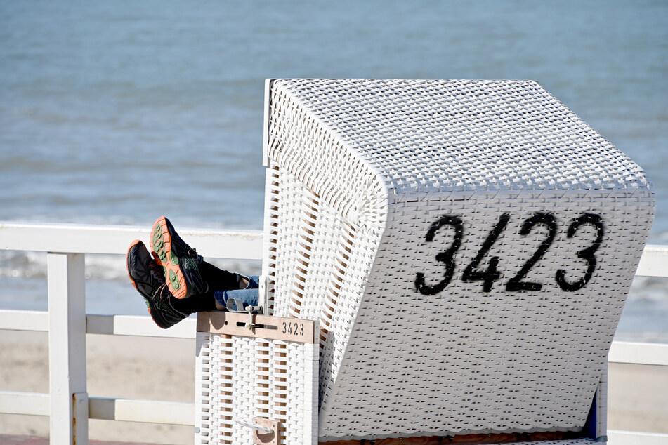Ein Mann sitzt bei sonnigem Wetter in einem Strandkorb an der Sylter Promenade.