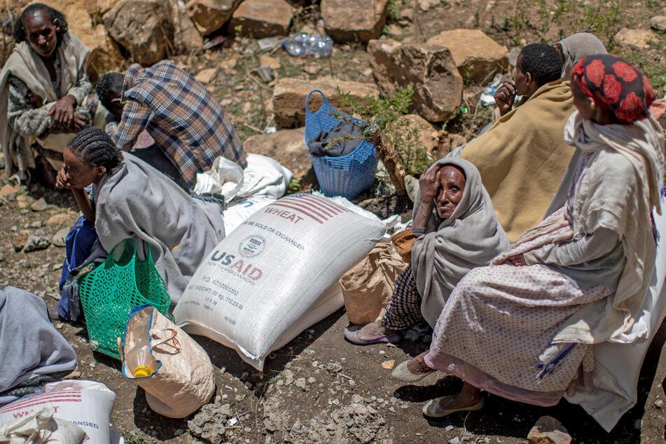 Eine ältere äthiopische Frau sitzt neben einem Sack Weizen, der zuvor in der Region Tigray im Norden Äthiopiens verteilt wurde.