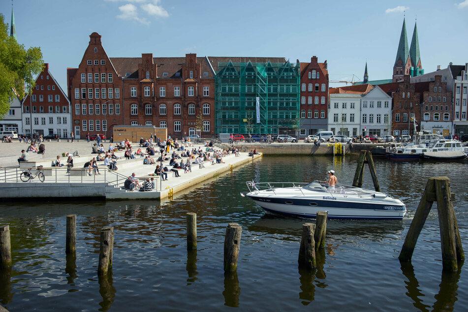 Menschen sitzen bei Sonnenschein auf Stufen am Ufer der Trave in Lübeck, während zwei Männer in einem Boot vorbeifahren.