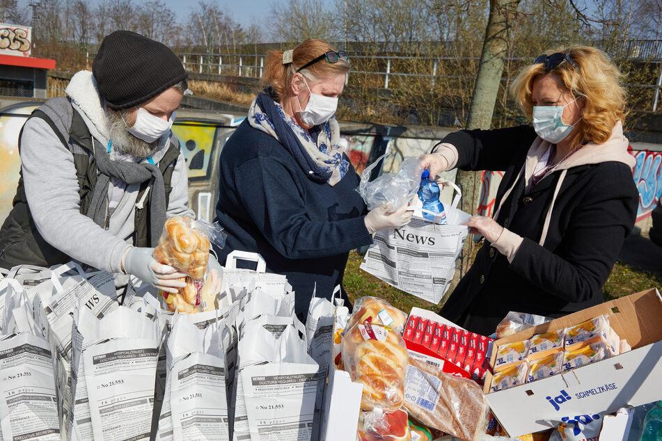 Helfer packen Lunch-Tüten für Obdachlose.