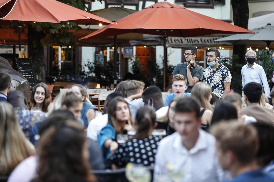 Jugendliche sitzen an Tischen auf der Terrasse eines Cafés. Angesichts steigender Corona-Zahlen hat Frankreichs Premierminister Castex an das Verantwortungsbewusstsein seiner Landsleute appelliert und warnte vor der wachsenden Ausbreitung des Virus im Land.