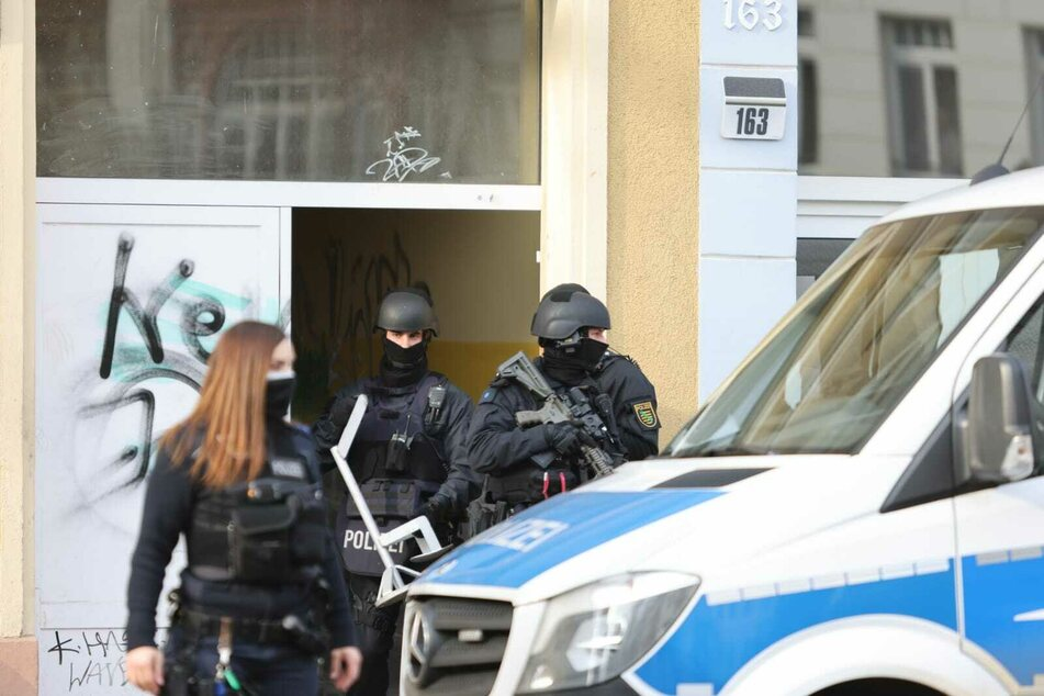 Einsatzkräfte des SEK verlassen ein Haus in der Wurzener Straße. Laut Polizei begleiten diese die anberaumten Durchsuchungen.