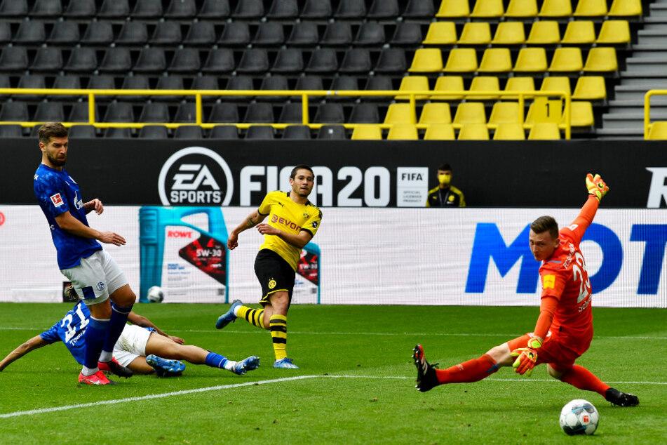 BVB-Flügelflitzer Raphael Guerreiro (Z.v.r.) überwindet Markus Schubert (r.) mit seinem platzierten Schuss und erzielt das 2:0 für Dortmund. Der S04-Keeper hatte das Tor mit seinem Fehlpass eingeleitet.