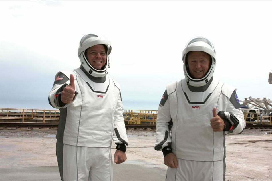 """Die NASA-Astronauten Robert Behnken (l.) und Douglas Hurley gestikulieren vor dem Einstieg in die Besatzungskapsel """"Crew Dragon"""" der """"Falcon 9""""-Rakete von SpaceX im Kennedy Space Center in Cape Canaveral."""