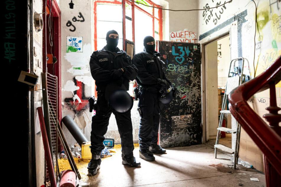 """Zwei Polizisten stehen nach der Räumung im Treppenhaus des ehemals besetzten Hauses """"Liebig 34""""."""