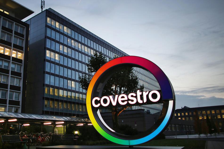 Das Logo des Kunststoffkonzerns Covestro leuchtet vor der Unternehmenszentrale am Chempark in Leverkusen.