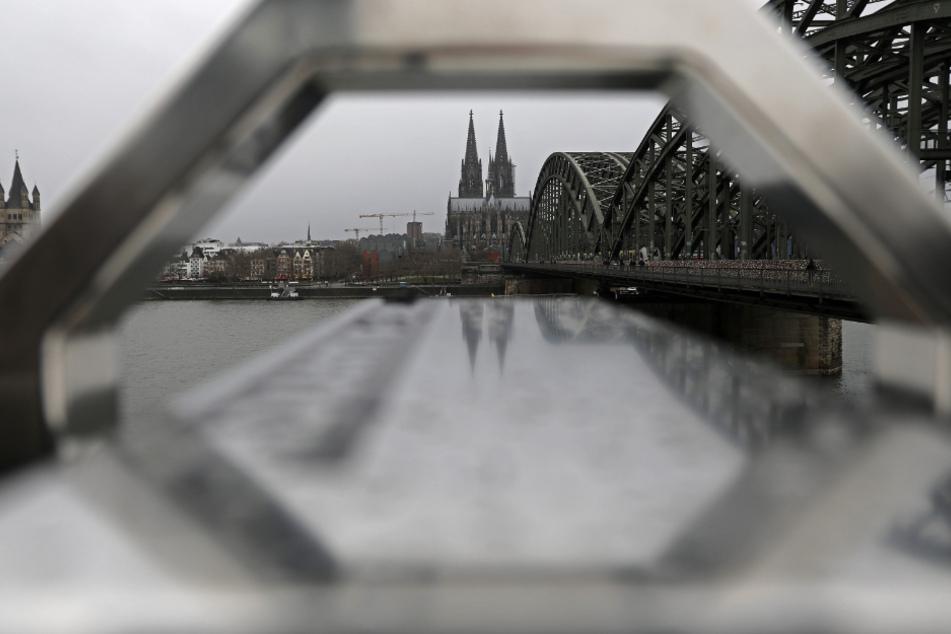 Der Kölner Dom und die Hohenzollernbrücke sind durch die Aufhängung eines Fernrohrs bei regnerischem Wetter zu sehen.
