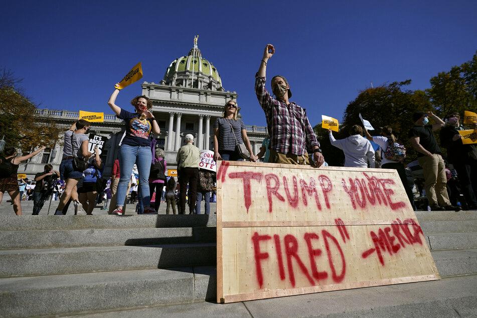 """Zahlreiche Menschen feiern vor dem Pennsylvania State Capitol und halten ein Plakat mit der Aufschrift """"Trump you're fired - Merica"""" (Trump, du bist gefeuert - Amerika"""".)"""