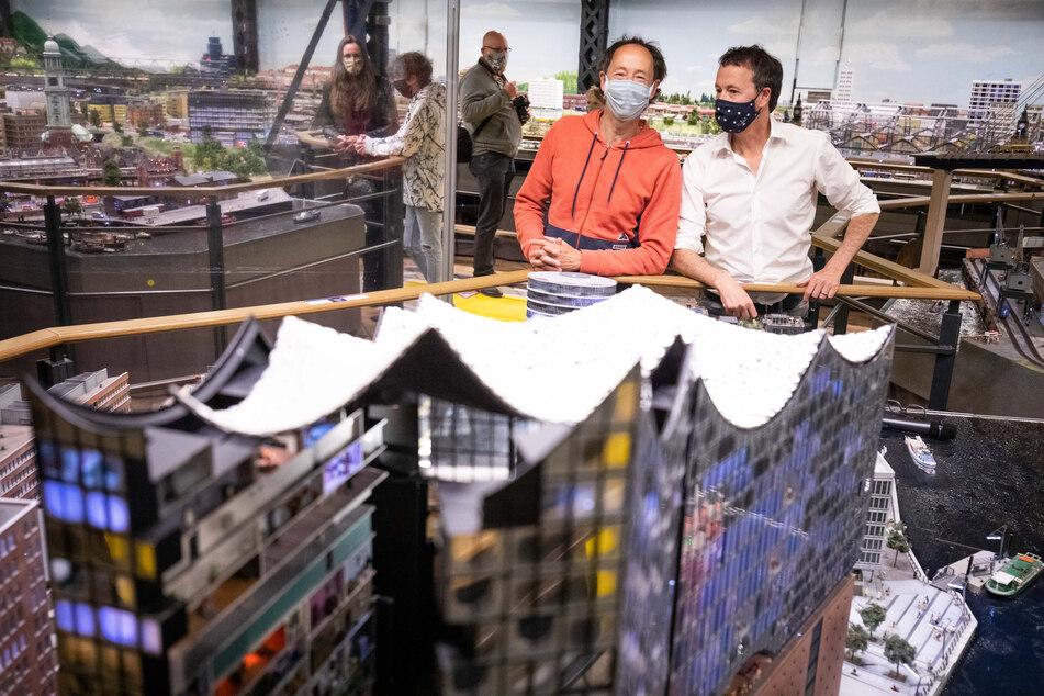 Frederik (r) und Gerrit Braun, Gründer und Geschäftsführer des Miniatur Wunderland stehen mit Mundschutz hinter dem Model der Elbphilharmonie.