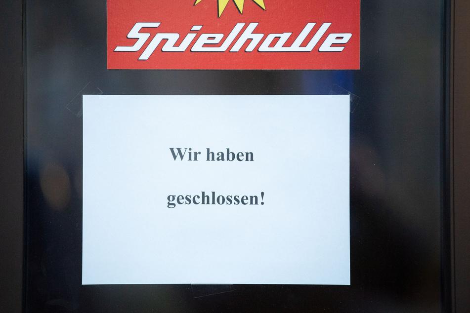 """Ein Schild mit der Aufschrift """"Wir haben geschlossen!"""" hängt am Eingang einer Spielhalle."""