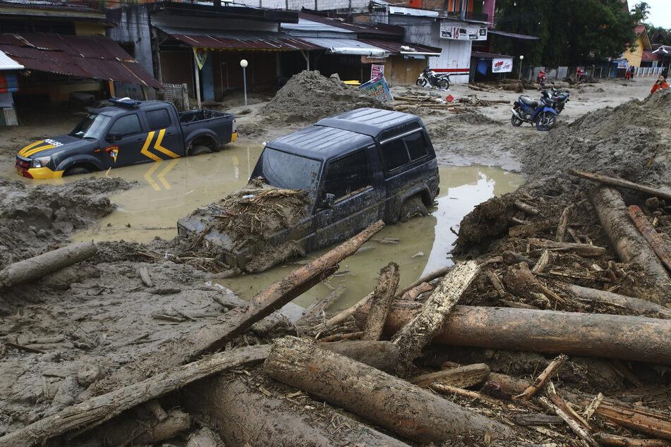 Indonesien, Masamba: Autos stecken im Schlamm fest in einem von einer Sturzflut betroffenen Gebiet in der Provinz Süd-Sulawesi.