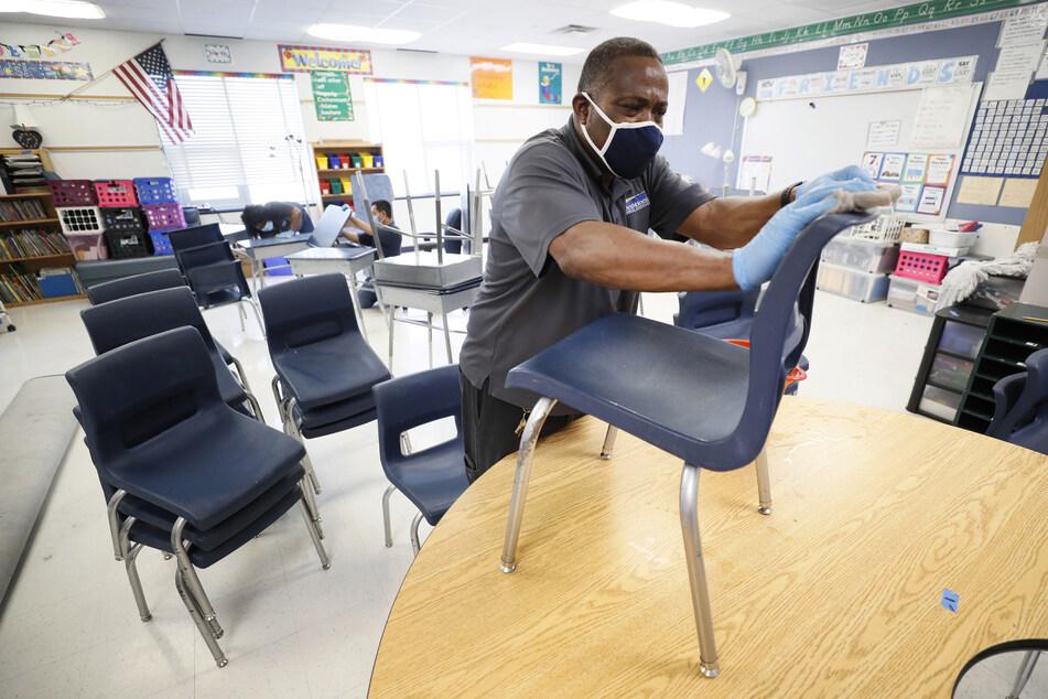 Tracy Harris reinigt in einem Klassenzimmer der Brubaker Grundschule Stühle. Nach scharfer Kritik von US-Präsident Trump will die Gesundheitsbehörde ihren Leitfaden für die Wiedereröffnung von Schulen überarbeiten. Trotz rapide steigender Fallzahlen dringt Trump auf eine Öffnung der Schulen im Land nach den Sommerferien.
