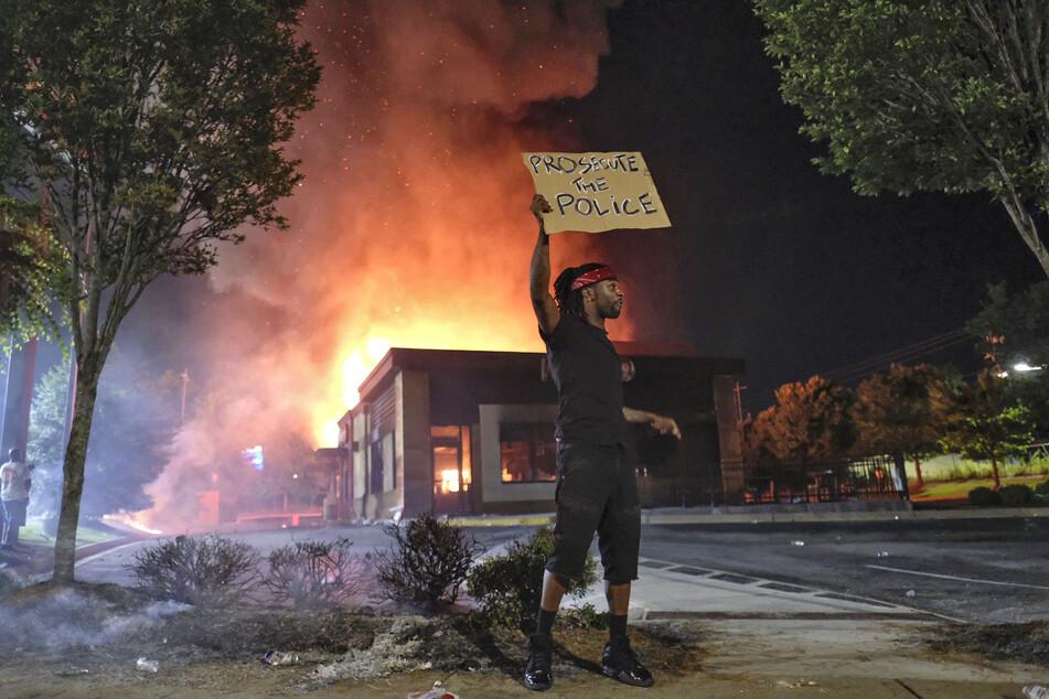 Ein Mann hält ein Schild, während im Hintergrund ein Wendy's-Restaurant brennt. Vor diesem wurde der 27-Jährige niedergeschossen.