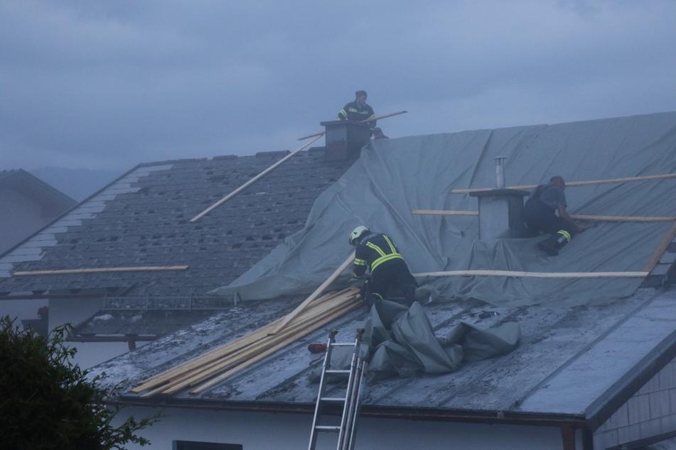 Feuerwehrleute arbeiten auf einem beschädigten Dach.