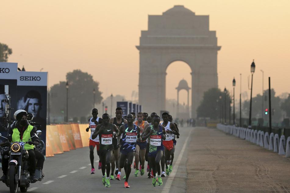 """Teilnehmer des Halbmarathons laufen vor dem """"India Gate"""" Denkmal auf der Strecke."""