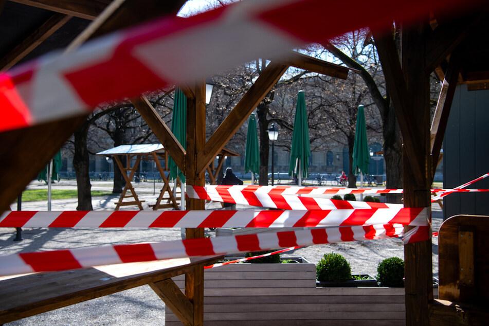 Tische und Stühle von einem geschlossenen Restaurant sind im Münchner Hofgarten mit Flatterband abgesperrt.