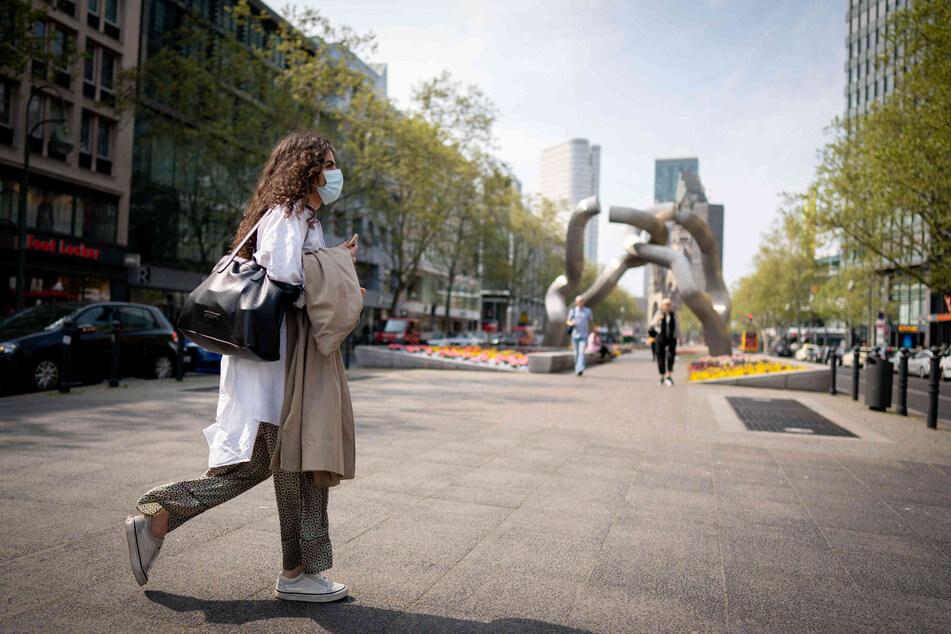 Eine Frau mit Mundschutz läuft über den Berliner Ku'damm.