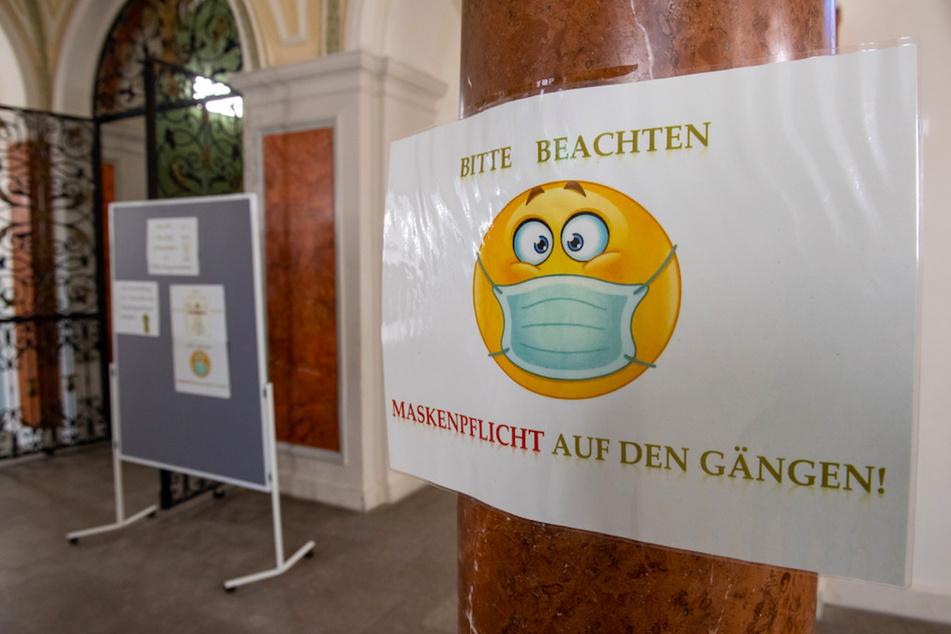 """Ein Schild mit der Aufschrift """"Bitte beachten - Maskenpflicht auf den Gängen!"""" hängt an einer Säule in einer Schule."""