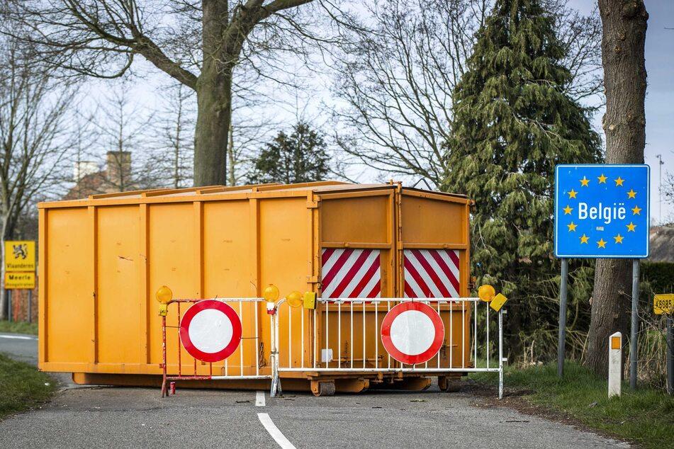 Ein Container und Absperrgitter blockieren eine Straße am Grenzübergang zwischen dem niederländischen Grazen und dem belgischen Meerle.