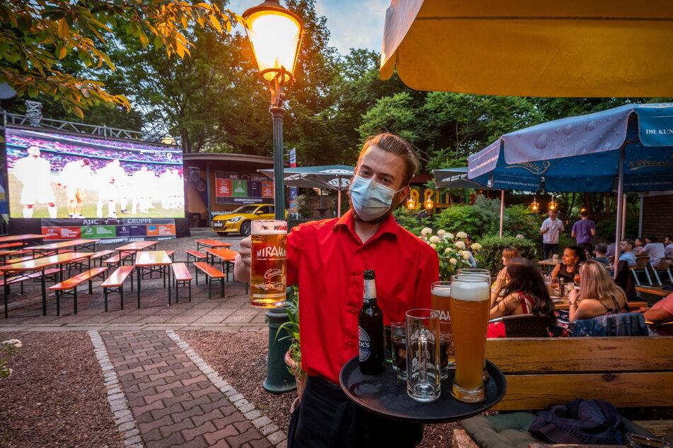 Kellner Felix Hähnel serviert den Gästen beim Public Viewing im Miramar kalte Getränke.