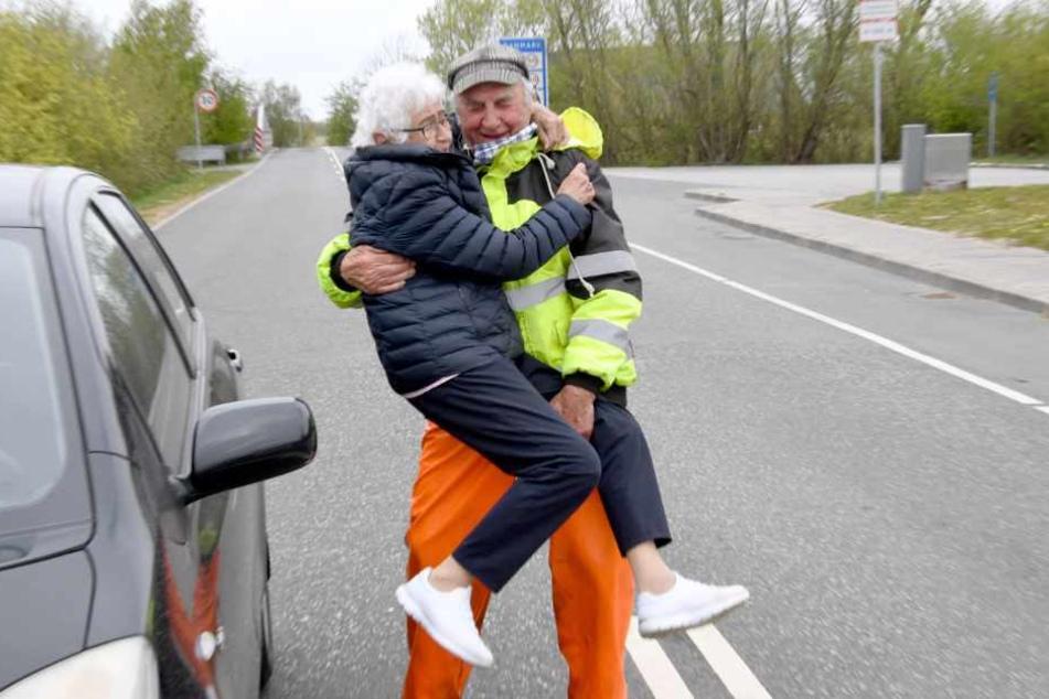 Inga Rasmussen aus Dänemark (85) wird von Karsten Tüchsen Hansen (89) aus Nordfriesland bei ihrem täglchen Treffen an der deutsch-dänischen Grenze hochgehoben.