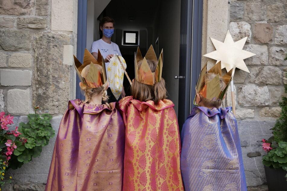 Kreativität in Corona-Zeiten: Mittels selbst gebasteltem Kescher nehmen drei Sternsinger eine Spende entgegen.