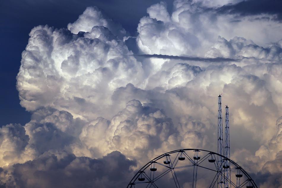 """Wolken türmen sich kurz vor Sonnenuntergang über den Fahrgeschäften des Freizeitparks """"Skylinepark"""" bei Kirchheim auf."""