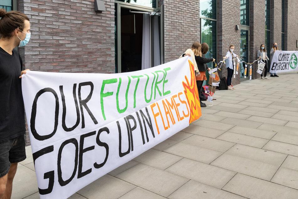 """Aktivisten der Bewegung """"Fridays for future"""" machen vor dem Veranstaltungsort auf den Klimaschutz aufmerksam."""