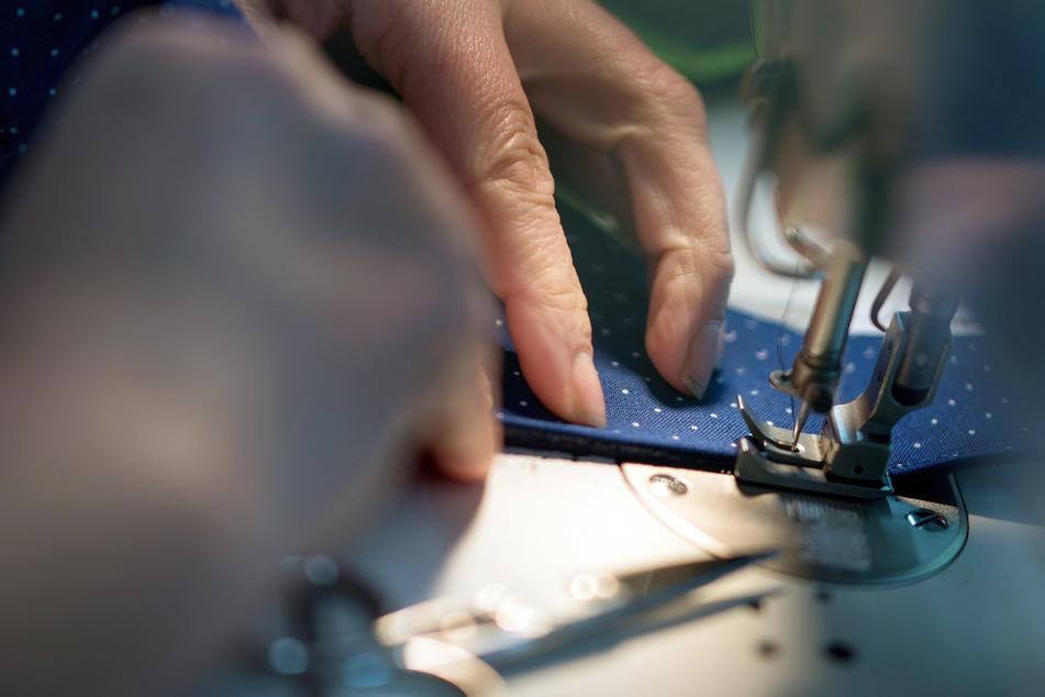 Eine Schneiderin arbeitet in der Produktion eines Modeherstellers an einer Nähmaschine.