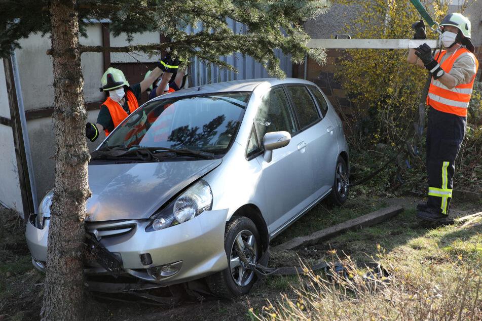Honda durchbricht Zaun und knallt gegen Baum und Schuppen