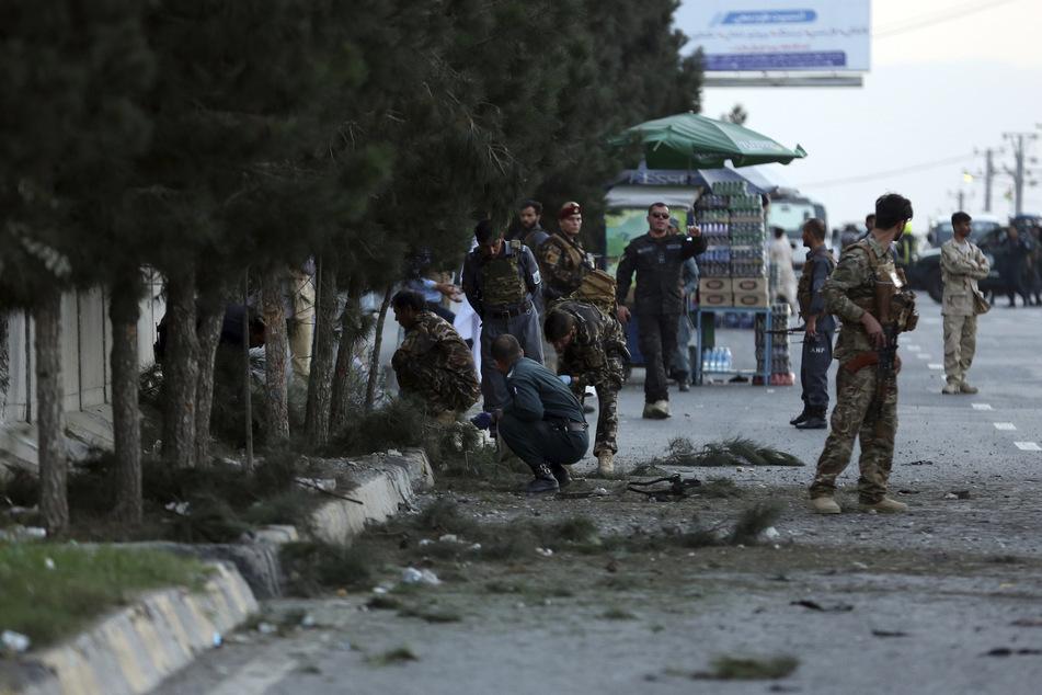 Afghanistan, Kabul: Sicherheitskräfte untersuchen an einer Straße den Ort einer Explosion.