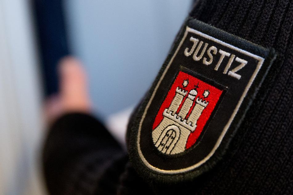Ein Justizbeamter steht in einem Gerichtsaal des Landgerichts Hamburg. Dort muss sich erneut ein 26-Jähriger verantworten, der mehrere Angriffe auf seine schwangere Freundin organisiert haben soll. (Symbolfoto)