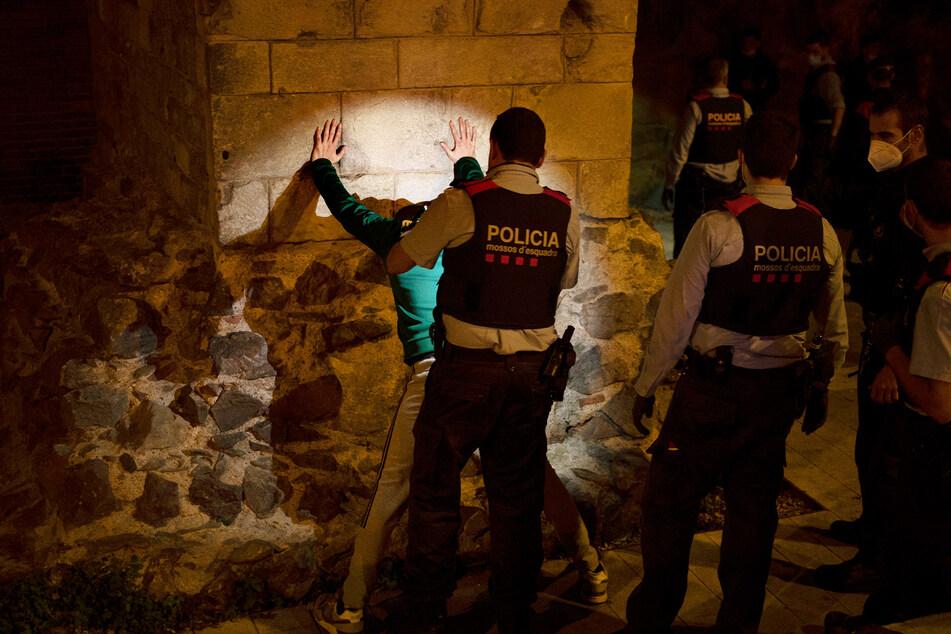 Polizisten kontrollieren einen Mann, der sich nicht an die nächtliche Ausgangssperre in Spanien hält.