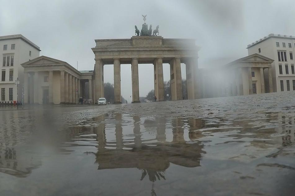 Das Brandenburger Tor spiegelt sich während eines Regenschauers in einer Pfütze.
