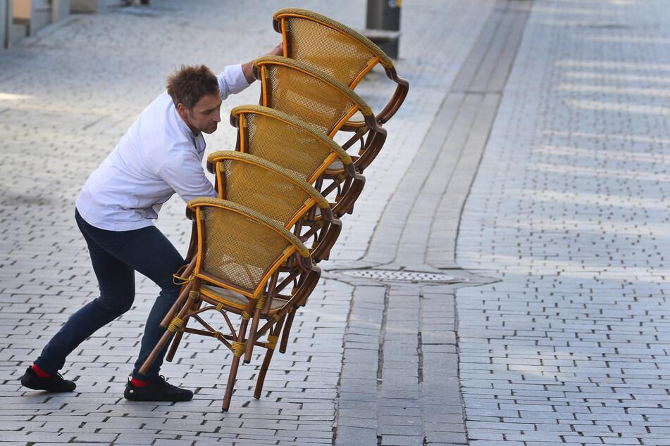 Ein Mitarbeiter eines Straßencafes trägt gegen 15 Uhr aufeinander gestapelte Stühle in sein Lokal. In der Corona-Krise haben viele Betriebe in Deutschland zur Kurzarbeit gegriffen.