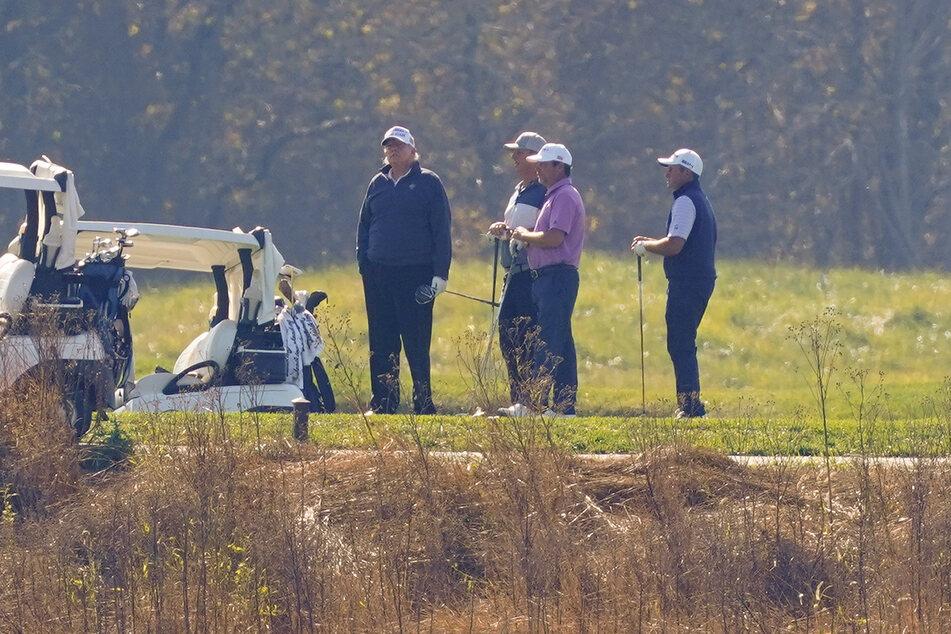 Donald Trump (l), Präsident der USA, nimmt an einer Golfrunde auf dem Trump National Golf Course teil, als er die Nachricht seiner Niederlage erhält.