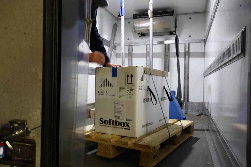 Ein Mitarbeiter einer Transportfirma steht auf der Ladefläche eines Kühltransporters und entlädt Kartons mit den ersten knapp 10.000 Impfdosen für Thüringen.