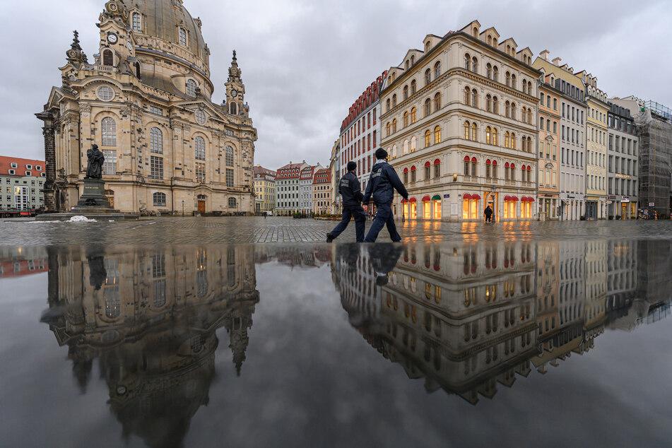 Sachsen, Dresden: Die Frauenkirche und die Häuser auf dem Neumarkt spiegeln sich am Nachmittag in einer nassen Steinbank während zwei Mitarbeiter der Polizeibehörde (Ordnungsamt) entlang laufen.
