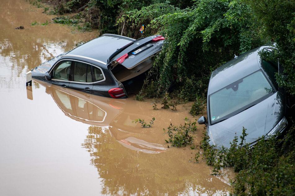 Autos stehen an der Böschung der überfluteten Bundesstraße in Erftstadt. Nach aktuellem Stand sind 43 Menschen durch das Unwetter in NRW gestorben.