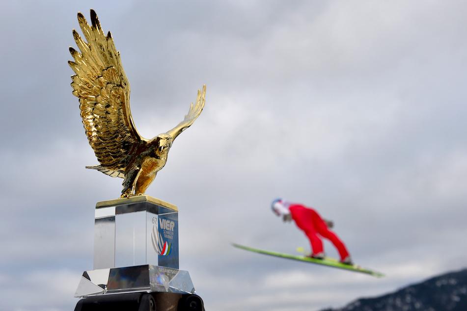 Ein Vorspringer springt hinter dem Pokal für den Gesamtsieger der Vierschanzentournee, dem goldenen Adler.