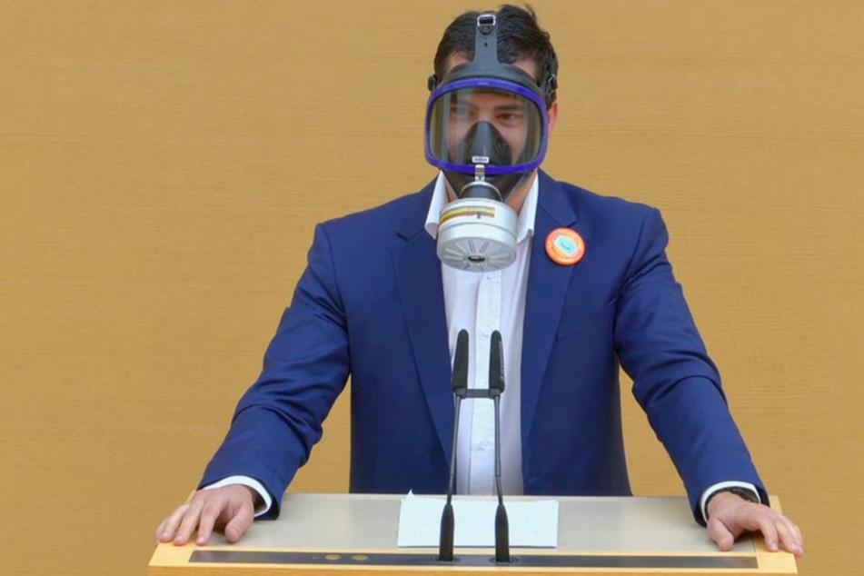 Der Screenshot aus einem Video zeigt den AfD-Abgeordneten Stefan Löw mit einer Gasmaske am Rednerpult im Bayerischen Landtag.