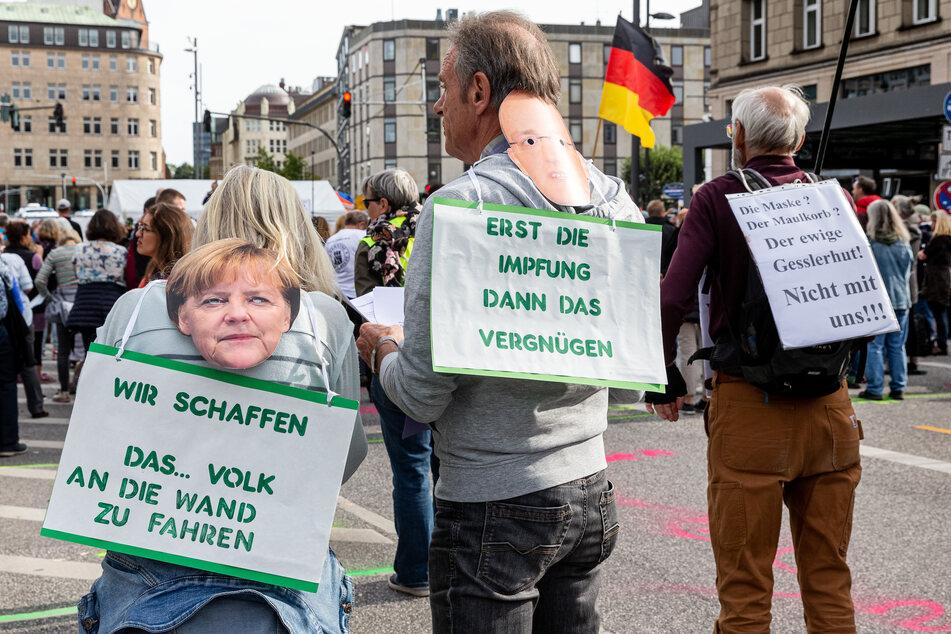 """Drei Demonstranten tragen Plakate mit den Aufschriften (l-r) """"Wir schaffen das ... Volk an die Wand zu fahren"""", """"Erst die Impfung, dann das Vergnügen"""" und """"Die Maske ? Der Maulkorb? Der ewige Geislerhut ! Nicht mit uns !!"""". Die Initiative Querdenken 40 demonstriert hier unter dem Motto """"Gemeinsam und gewaltfrei für die Aufhebung der Coronamaßnahmen""""."""