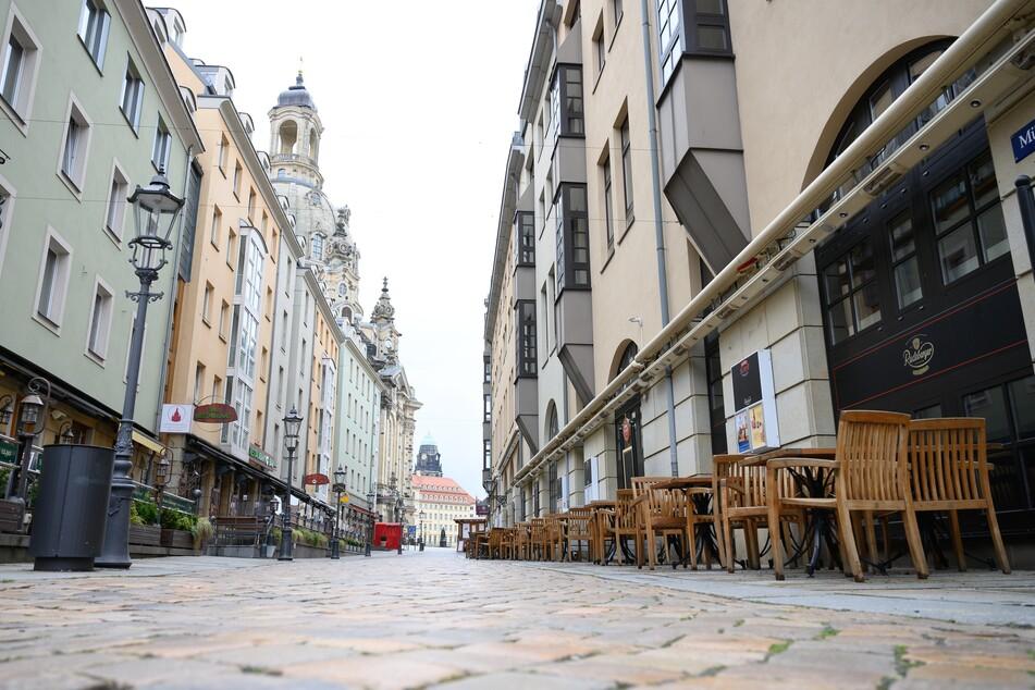 Leere Tische und Stühle stehen vor noch immer geschlossenen Lokalen auf der Münzgasse in Dresden.