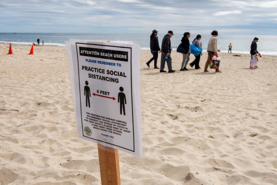 Schilder am Hauptstrand erinnern Strandbesucher daran, wegen der Corona-Krise den vorgeschriebenen Mindestabstand von sechs Fuß (etwa 1,8 Meter) zu halten.