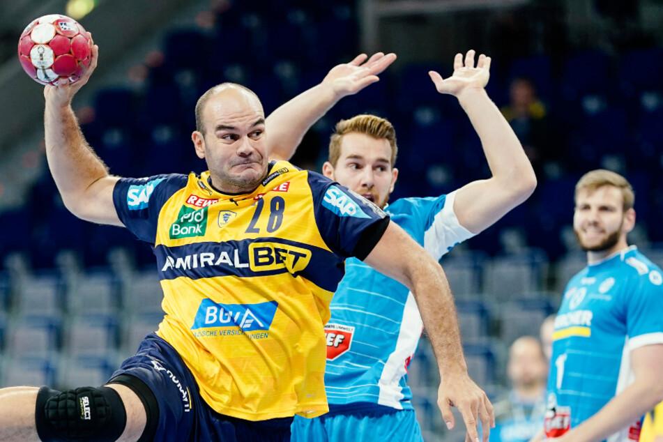 Rafael Baena Gonzalez (l) von den Rhein-Neckar Löwen wirft an Stuttgarts Rudolf Faluvegi vorbei ein Tor. Der Handballverband Baden-Württemberg stellt den Betrieb ein.